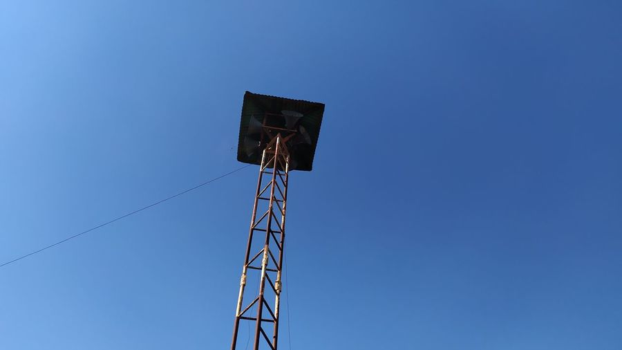 Low angle view of communications tower against clear blue sky