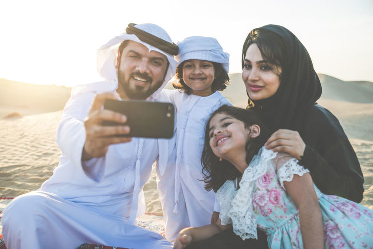 Happy family taking selfie with phone at desert
