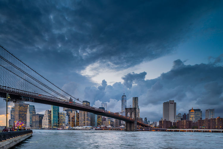 Low angle view of brooklyn bridge over river against cloudy sky in city
