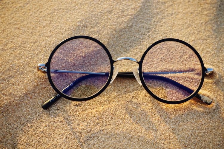 High angle view of eyeglasses on sand