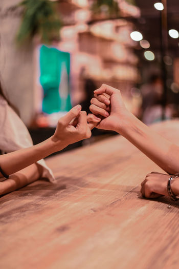 Cropped hands of female friends doing pinky promise at table in restaurant
