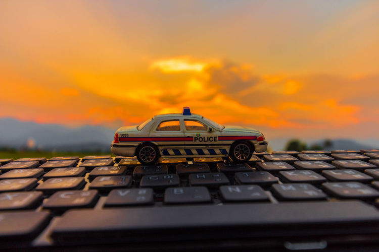 Close-up of toy car on roof against sky during sunset