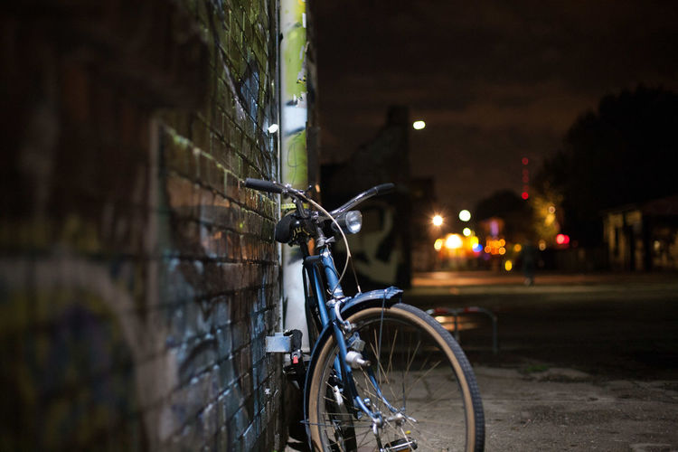 Bicycle parked on street by building at night