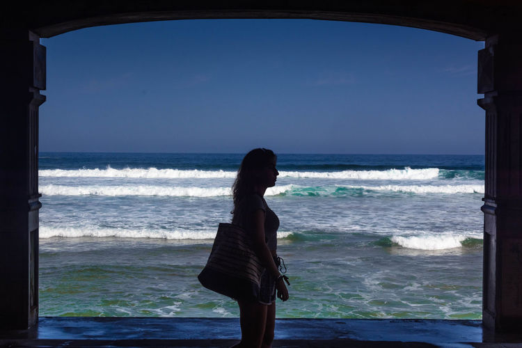 Side view of woman standing at entrance by sea against sky