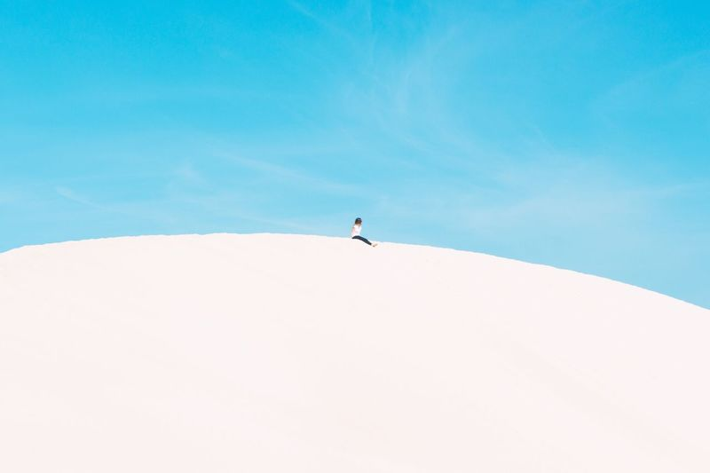 Low angle view of woman sitting on sand dune against clear sky