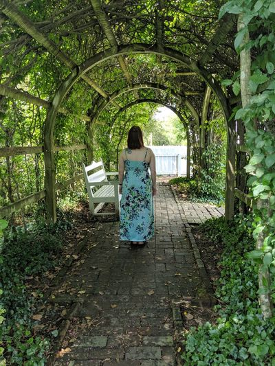 Rear view of woman standing below arch pergola