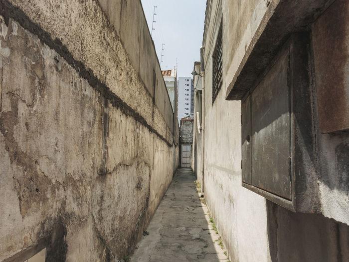 Walkway amidst buildings against sky