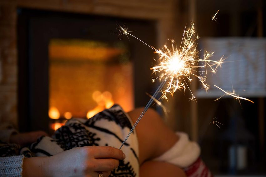 woman hands holding sparklers by fireplace Woman Hands Hand Holding Sparkler Sparkle Sparkles Fireplace Mountain Cabin Cabin Life Rustic Cabin Style Cozy Blanket Cold December New Year New Year New Year Eve Celebration Burning Blurred Motion Illuminated Human Hand Firework Sparks