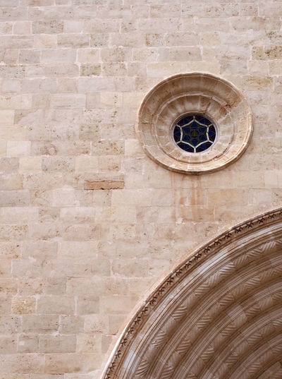 architectural medieval stone wall background with an ornate round window and section of a large carved curved ach Architecture Arch Building Exterior Religion Place Of Worship Spirituality Built Structure Wall - Building Feature Wall Architectural Feature Low Angle View History Outdoors Stone Wall The Past Window Travel Destinations Ornate