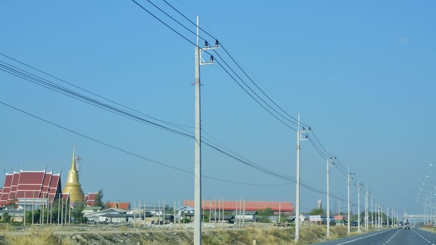 Electricity pylons against clear blue sky