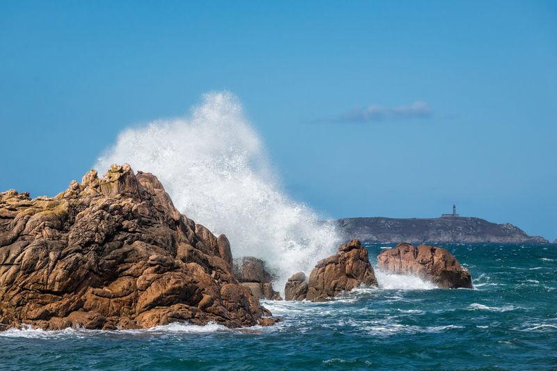 Waves splashing on sea against blue sky