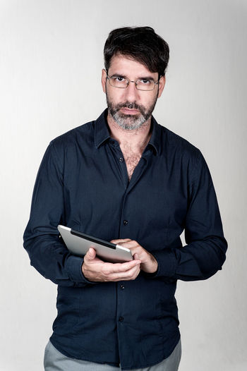 Portrait of serious mature man with digital tablet against white background