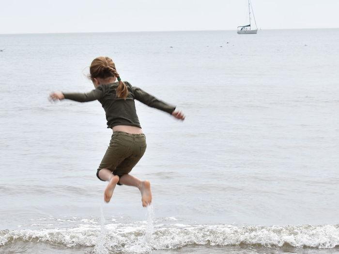 Full length of girl jumping on beach