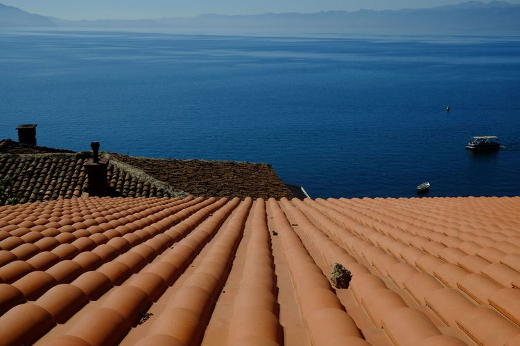 High angle view of roof by sea against sky