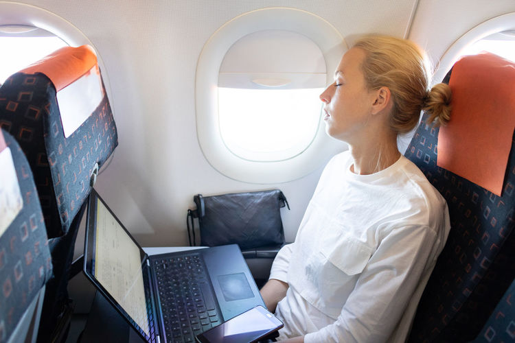 Businesswoman sleeping while sitting in plane