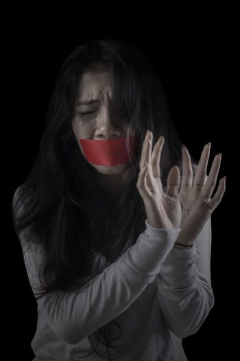 Scared woman with duct tape against black background