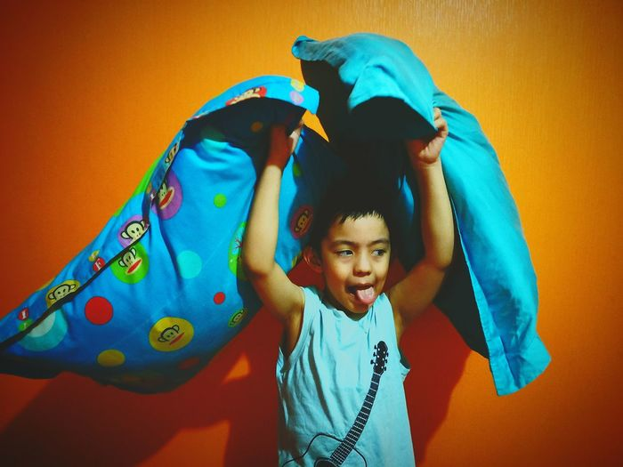 Cute Boy With Blue Pillows Standing Against Orange Background