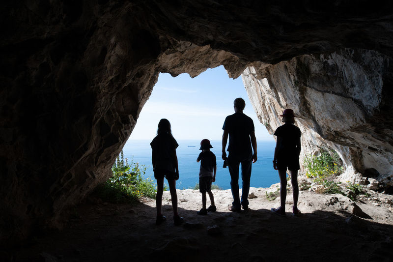 Silhouettes of tourists standing in the entrance of a cave