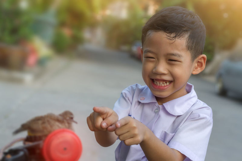 Cheerful boy pointing at bird outdoors