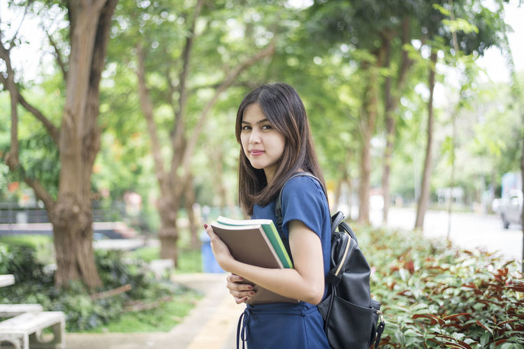 Beautiful Woman Book Campus Casual Clothing Day Education Leisure Activity Lifestyles Long Hair Looking At Camera Nature One Person Outdoors Park - Man Made Space Portrait Real People Relaxation Smiling Student Tree University Student University Study Young Adult Young Women Investing In Quality Of Life