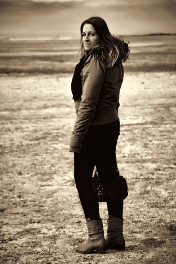Full Length Portrait Of Smiling Woman Standing On Field