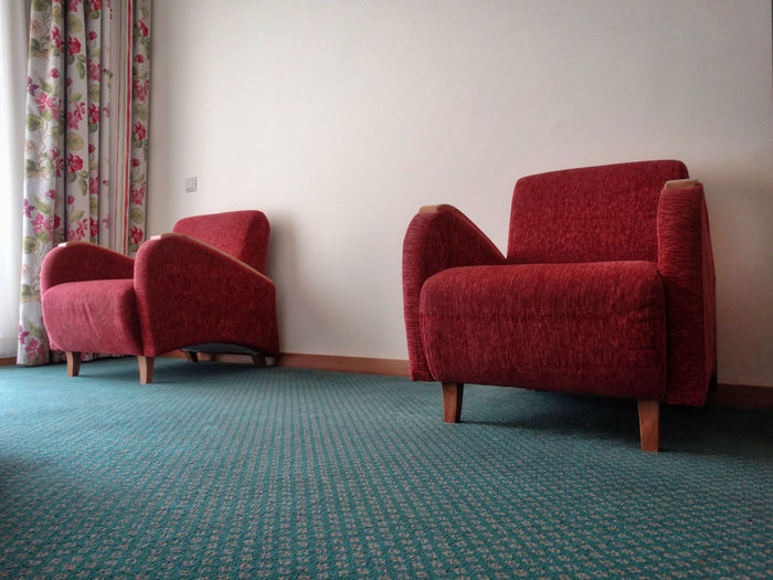 Hotel room chairs. Chair Seat Indoors  Empty Absence Furniture Domestic Room Living Room Home Interior No People Red Flooring Sofa Armchair Stuffed Relaxation Day Wall - Building Feature Home Showcase Interior Chairs Hotel Hotel Room Carpet Decor