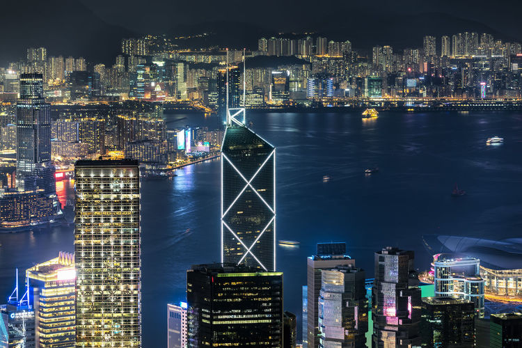 View to the skyline of Hongkong with the illuminated skyscrapers by night Architecture Building Exterior City Built Structure Illuminated Night Cityscape Travel Destinations Skyscraper Financial District  Modern Office Building Exterior Water Building China HongKong Skyline Lights Victoria Harbour Bay Kowloon Tourist Attraction  Cityscape Urban Futuristic