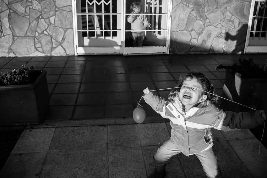 A girl plays with her balloon in a glider club in Rosario, Argentina, while her little friend is watching her from a safe position. Children play here every weekend while their parents maneuver their motor free aircrafts through the thermals, fix them inside their hangars or relax during a BBQ. The Photojournalist - 2016 EyeEm Awards The Photojournalist – 2016 EyeEm Awards The Street Photographer – 2016 EyeEm Awards The Street Photographer - 2016 EyeEm Awards Girl Power
