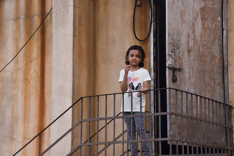 Portrait of a girl standing against railing