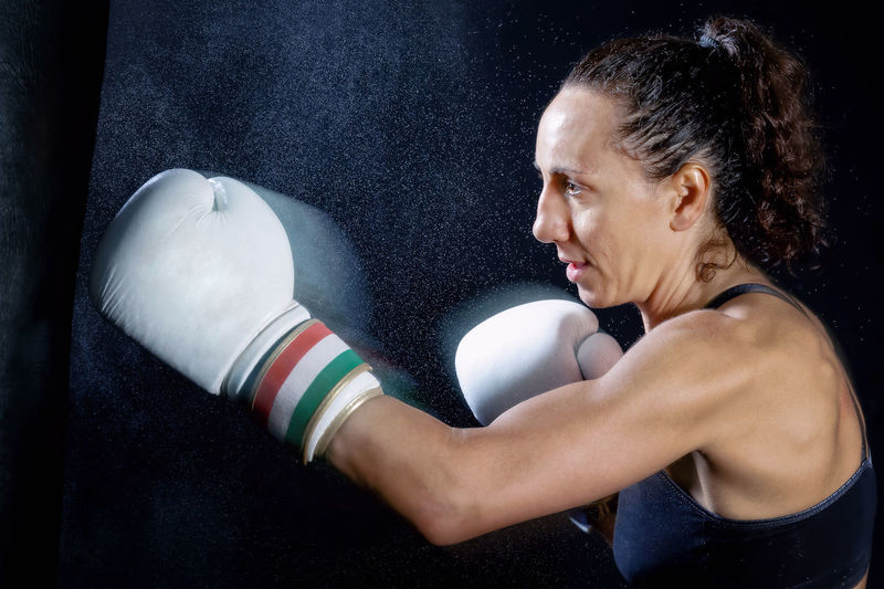 Female Boxer Punching Bag Against Black Background