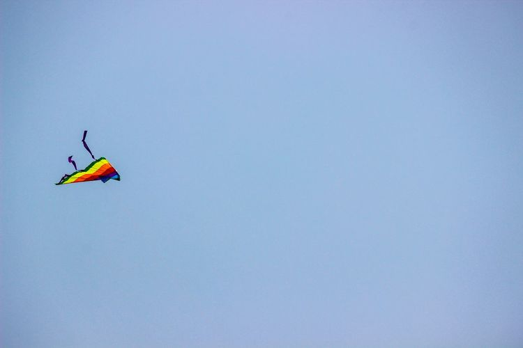 Low angle view of colorful kite flying in clear blue sky