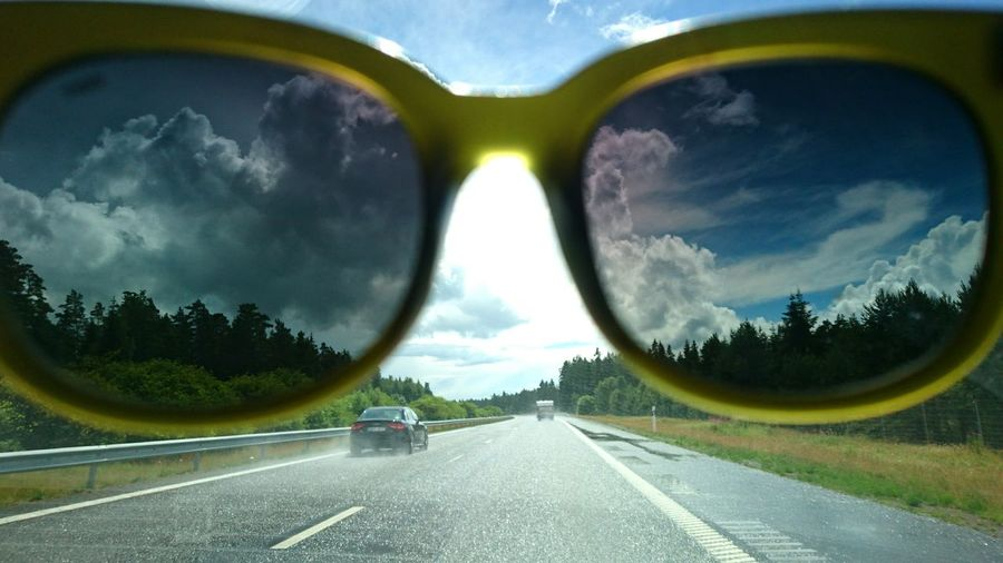 Sky seen through sunglass over road