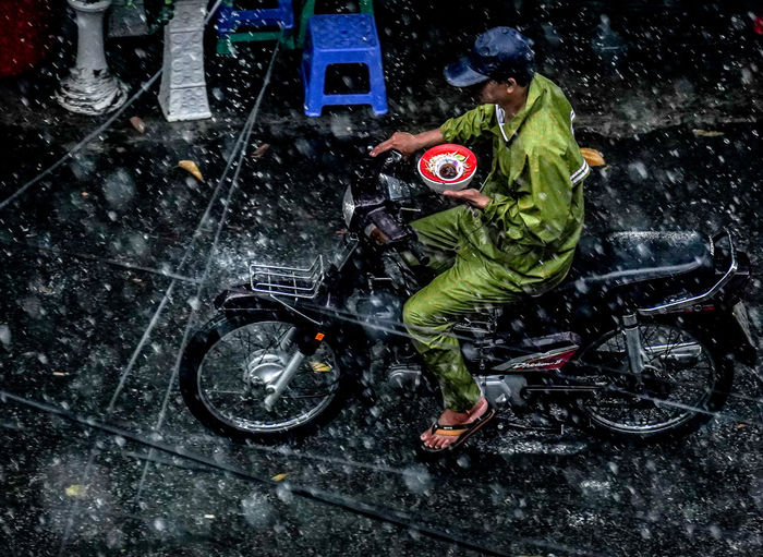 High angle view of man on wet car during winter