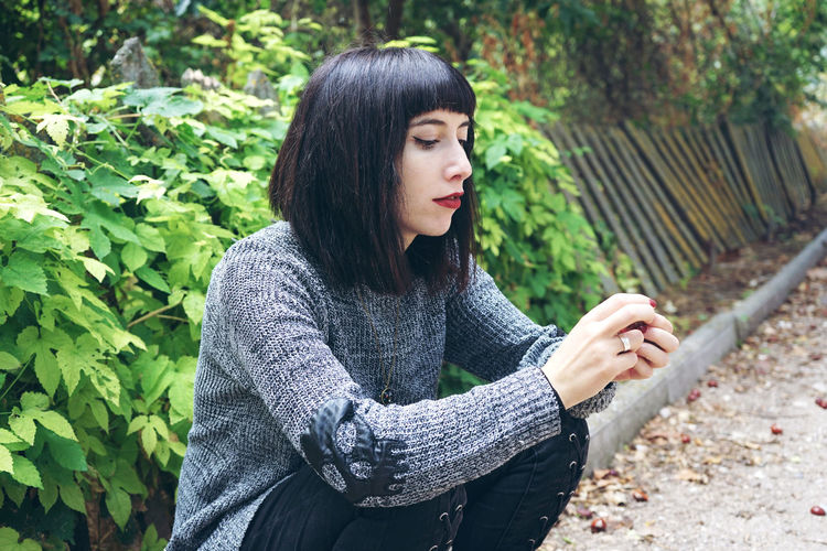 Woman Sitting On Footpath Against Plants