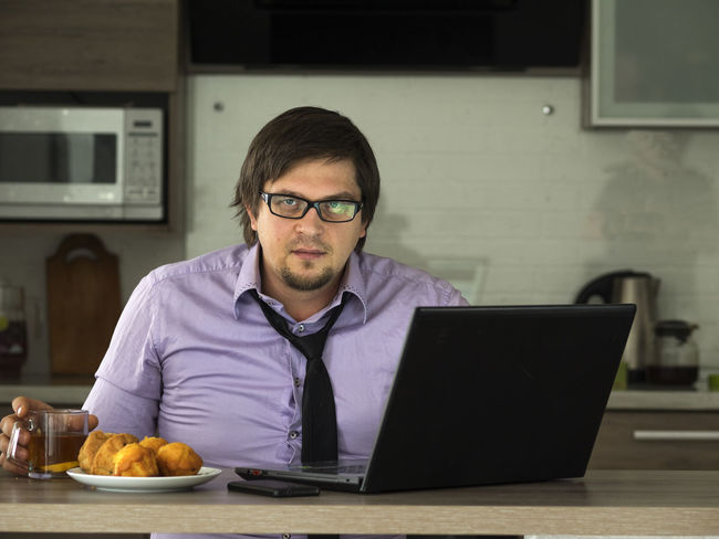 Young businesman drinkig tea and looks information in social media on net-book Adult Adults Only Beard Businesman Caucasian Connection Eyeglasses  Front View Headshot Indoors  Internet Laptop Looking Men One Man Only One Person Only Men People Sitting Technology Using Laptop Wireless Technology Working Young Young Adult