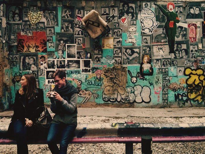 Friends sitting on rod against graffiti wall