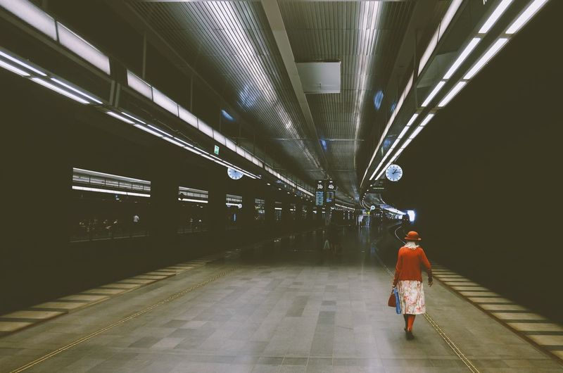 Rear view of man walking on railroad station