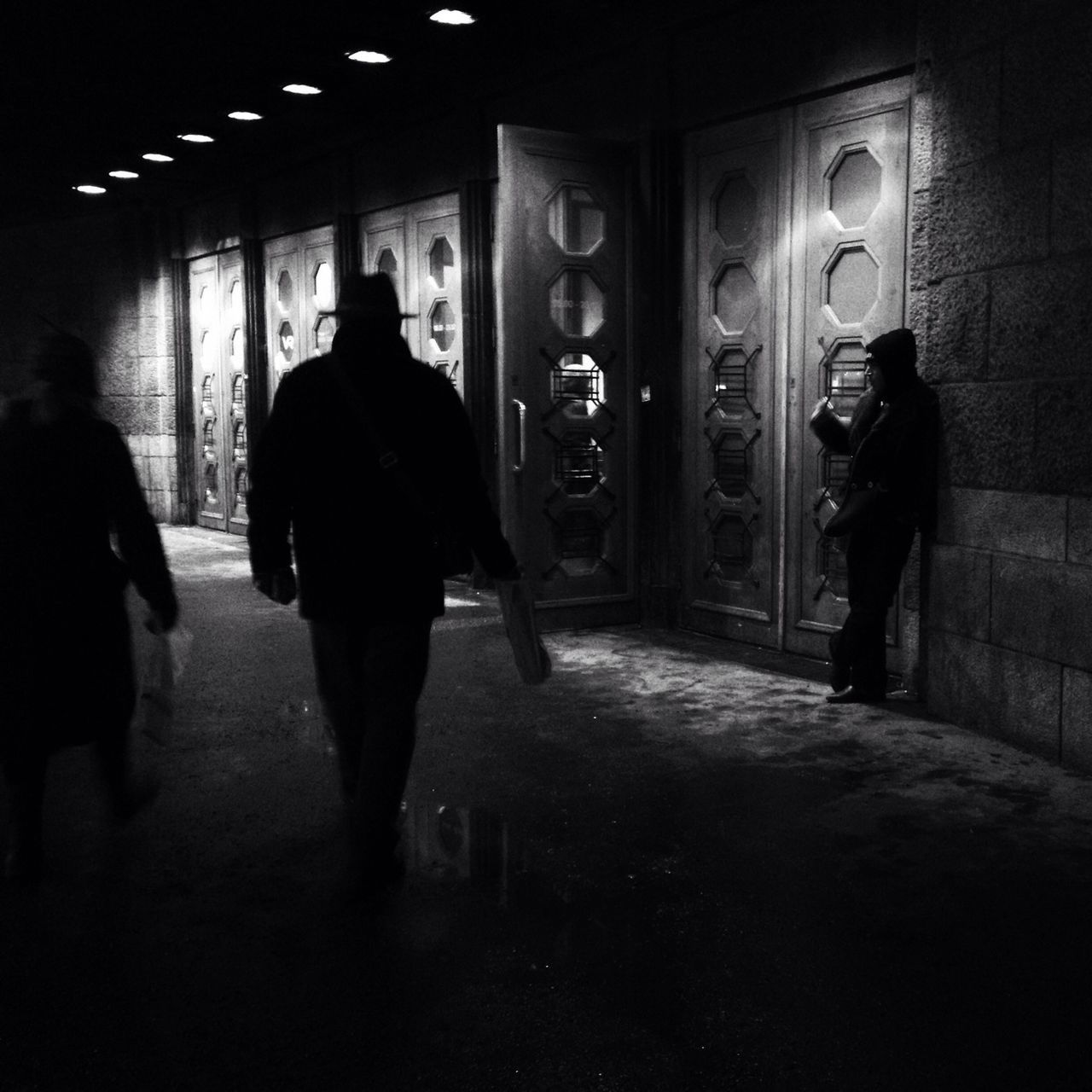 Silhouette People On Street Against Building At Night