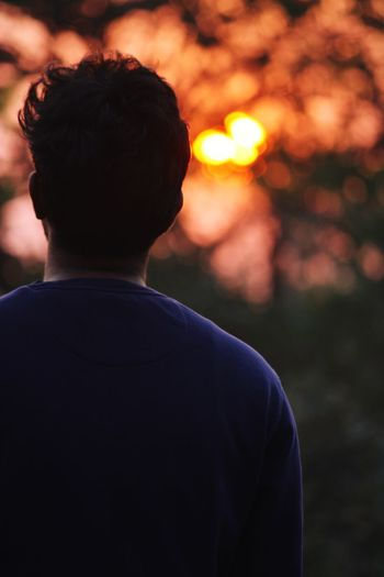 Rear view of man standing against orange sky
