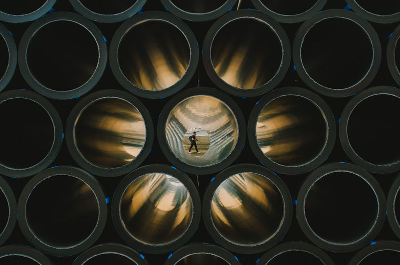 Man Walking At Beach Seen Through Stacked Pipes