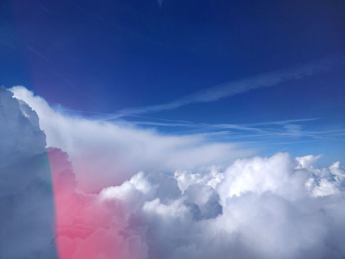 View From Airplane Over White Clouds Against Blue Sky