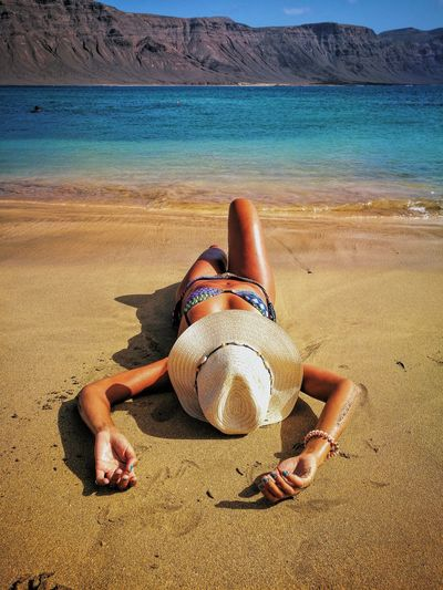 Midsection of woman lying on sand at beach