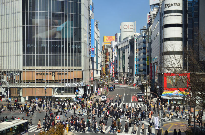 Crowd on street in city against sky