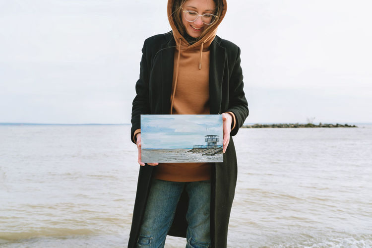 Smiling woman holding painting against sea