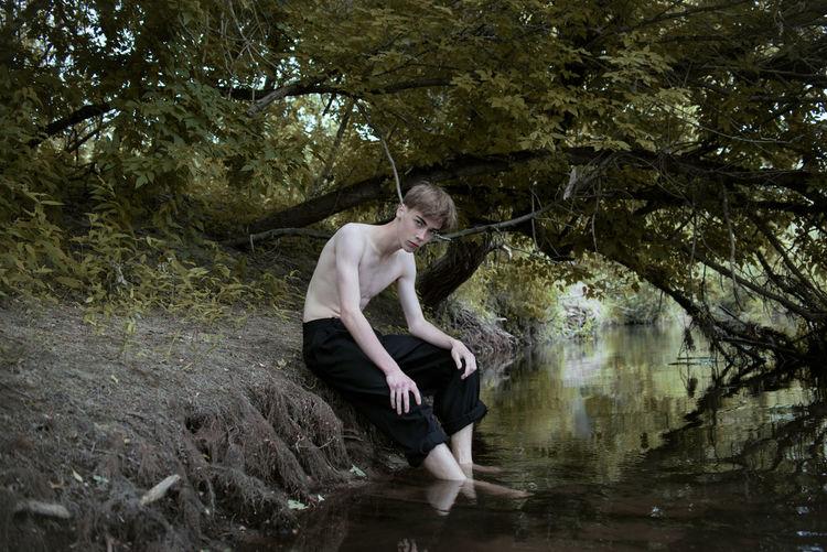 Portrait of man sitting by lake
