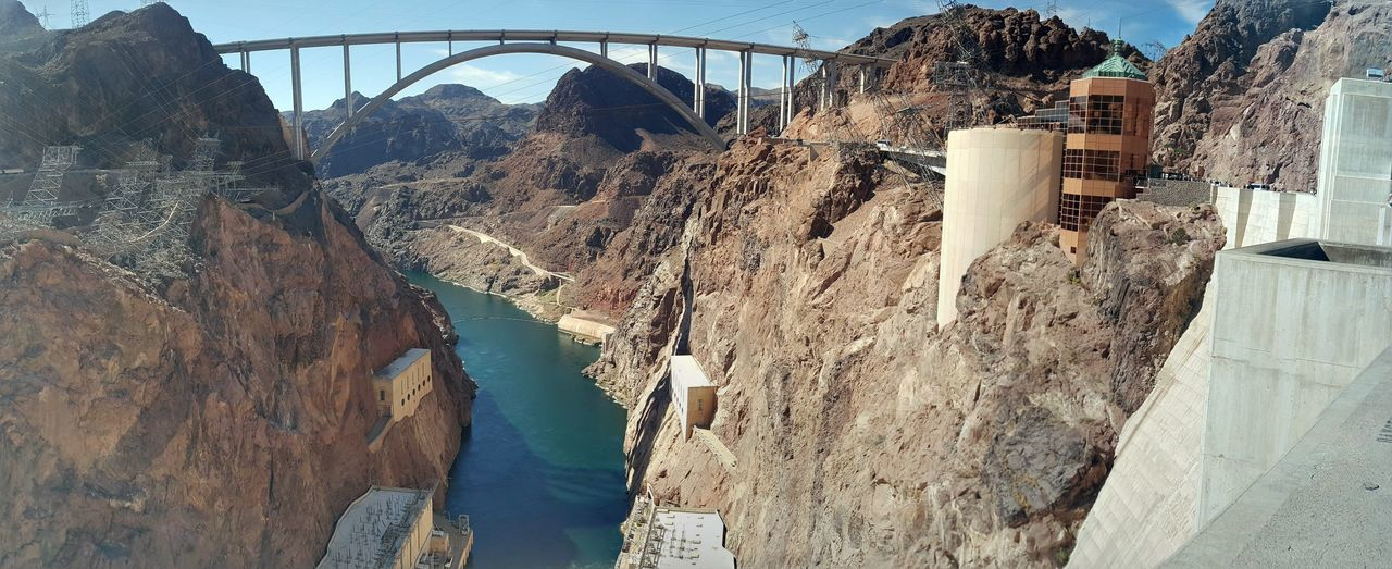 architecture, built structure, dam, hydroelectric power, bridge - man made structure, day, rock - object, connection, water, no people, mountain, outdoors, nature, building exterior, sky