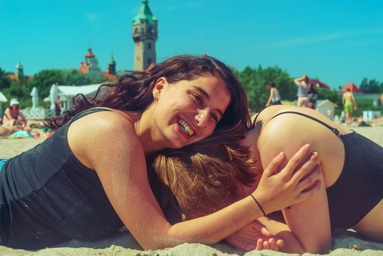 Cheerful friends lying on sand at beach during sunny day