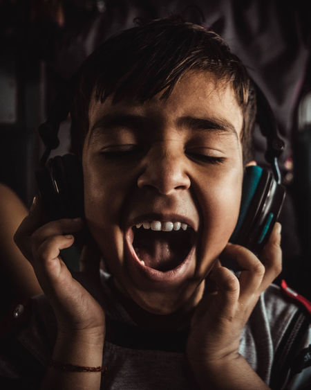 Close-up of boy with mouth open listening music through headphones