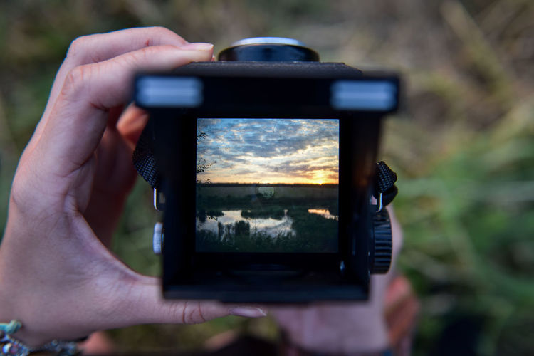 Cropped hands of woman photographing swamp against cloudy sky