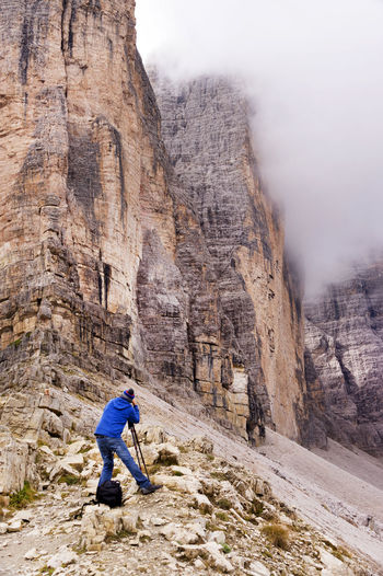 Rear View Of Man Photographing Tre Cime Di Lavaredo At Dolomites During Foggy Weather